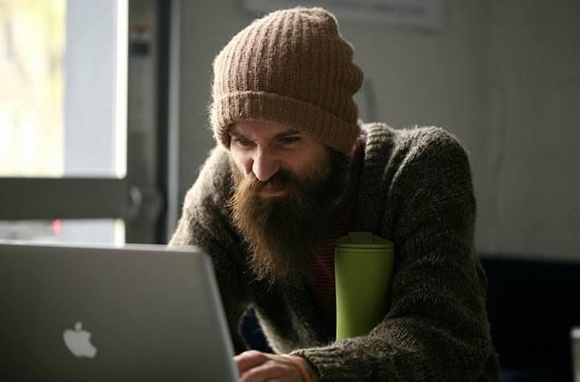 Бородатый мужик зарабатывает деньги на блоге
