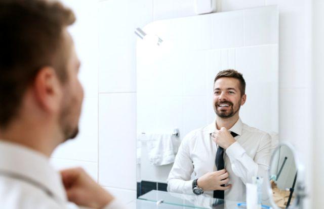 Улыбающийся бизнесмен готовится к рабочему дню перед зеркалом