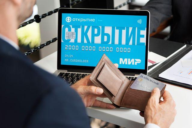 Бизнесмен выбирает дебетовую карту для бизнеса с помощью ноутбука