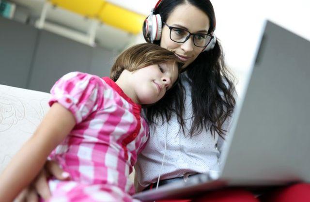 Молодая женщина с дочерью сидит перед ноутбуком и выполняет свою работу
