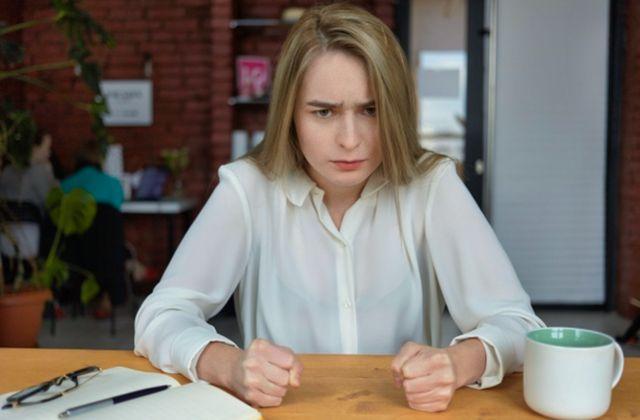 Рассерженная девушка сидит за столом с чашкой и книгой