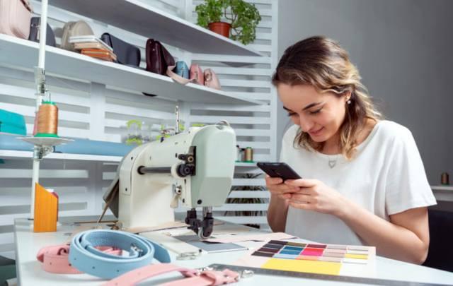 Девушка за швейной машинкой увлечено изучает публикации в социальной сети