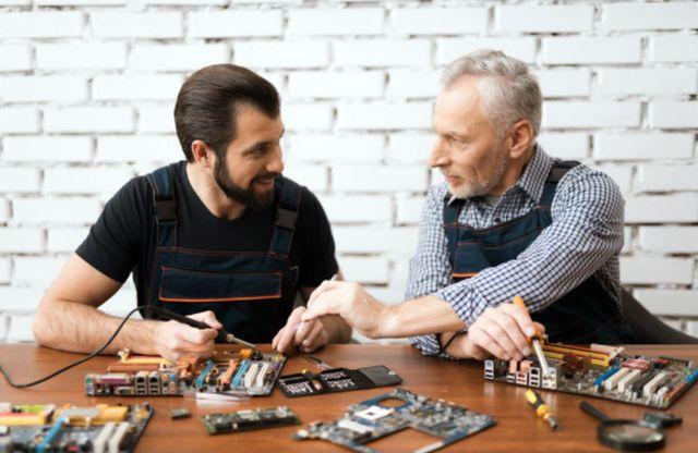 Пожилой сотрудник делится опытом работы по ремонту компьютерных микросхем